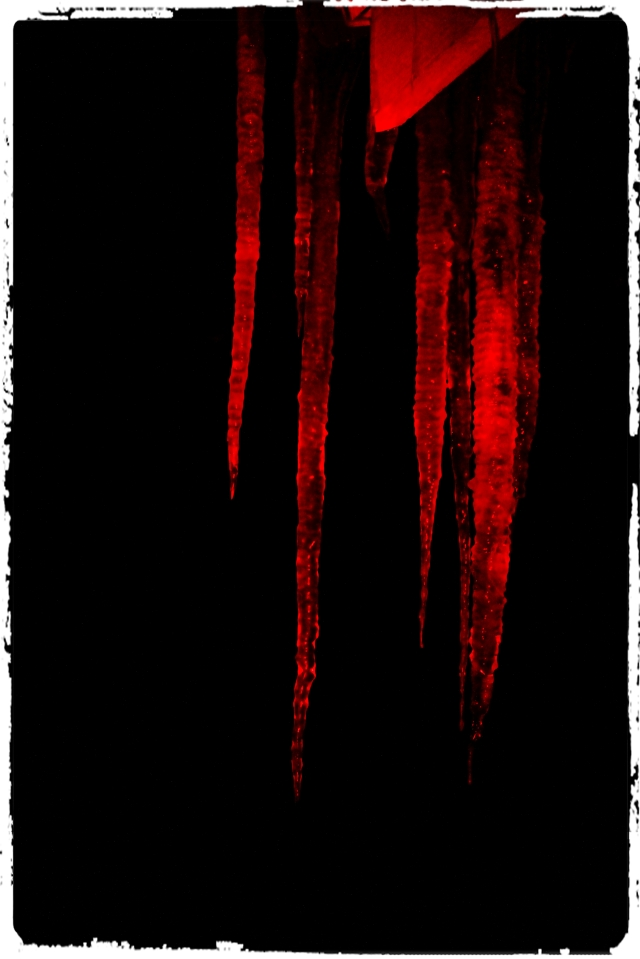 Icicles with red spotlight shining on them.
